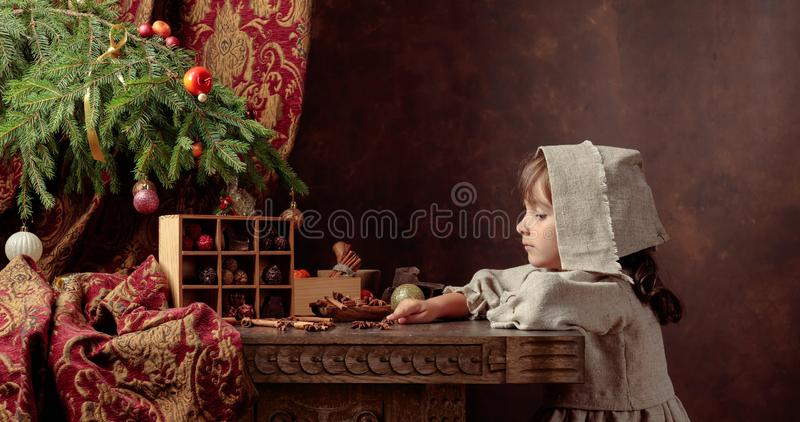 Little girl in an vintage linen dress near the table with sweets. Genre portrait in retro style stock images