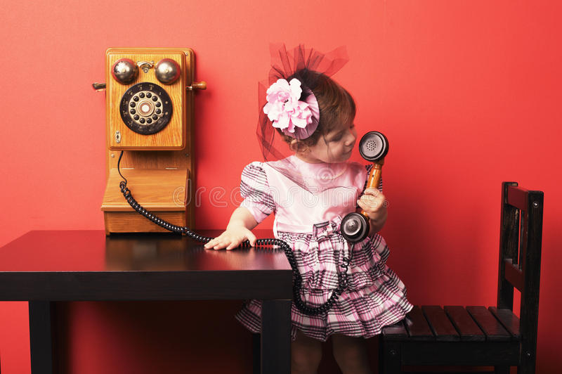 Little girl with vintage phone stock images