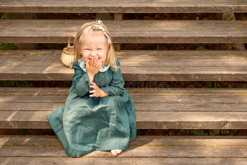 Little Girl In Vintage Retro Style Linen Dress Barefoot Sitting And  Laughing On A Wooden Stairs In The Park With Wicker Basket