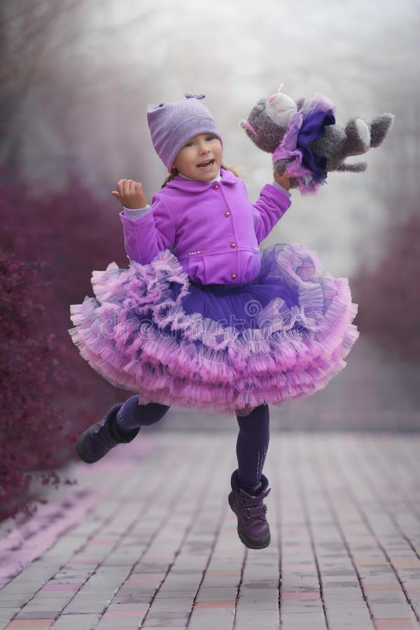Little girl in the violet dress dancing with a toy cat. Dance in the imaginary fairyland stock image