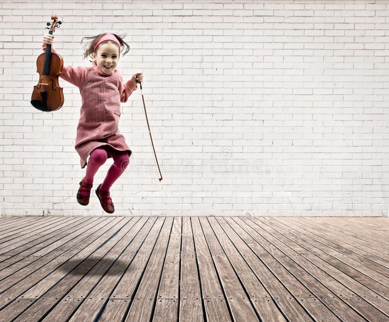 Little girl with violin jumping stock images