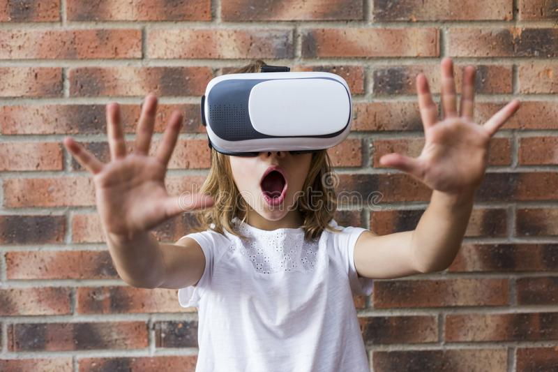 Little girl with virtual reality headset. Innovation technology and education concept. Brick background royalty free stock image