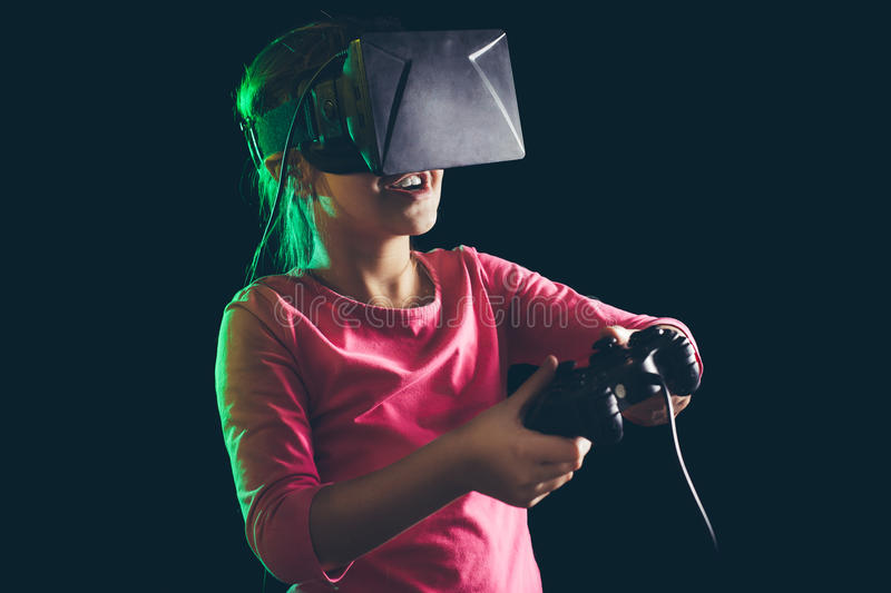 Little girl in virtual reality headset playing video-game stock photos