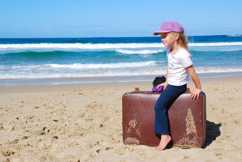 Child traveling with suitcase. A cute little Caucasian girl child sitting barefoot on a suitcase on the beach waiting for holiday departure in summertime stock images