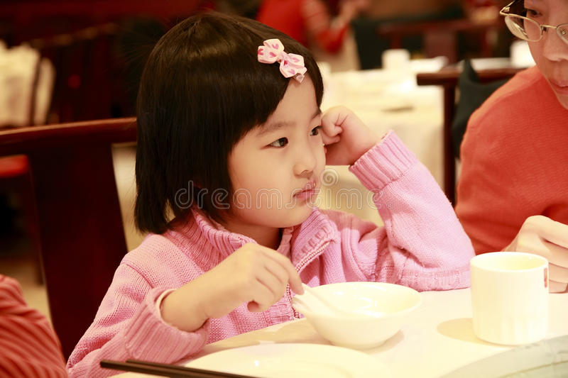 Little girl waiting for lunch. Little cute asian girl is waiting for lunch in a restaurant.She told her mother she was hungry royalty free stock photo