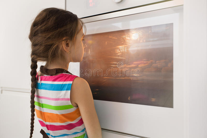 Little girl waiting near the kitchen oven for homemade cookies royalty free stock photos