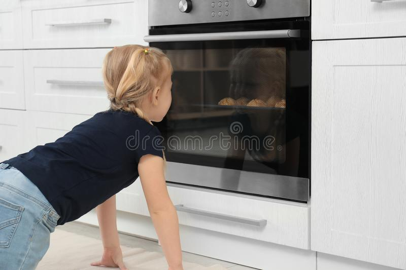 Little girl waiting for preparation of cookies in oven. At home stock images