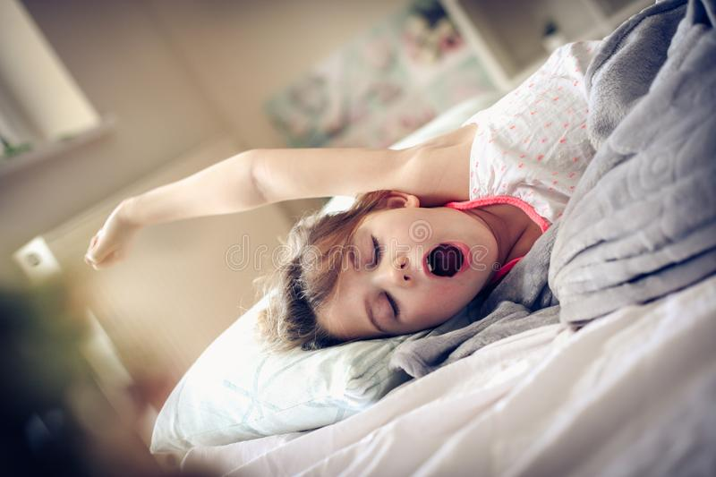 Awakening. Little girl wake up in bed. Space for copy stock photography
