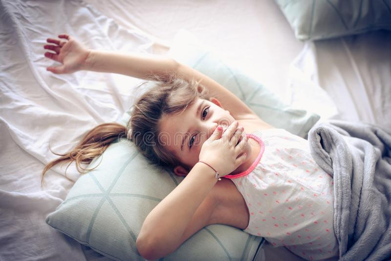 I am tired. Little girl wake up in bed. Space for copy stock photo