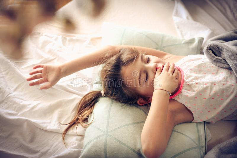 Morning in bed. Little girl wake up in bed. Space for copy stock image