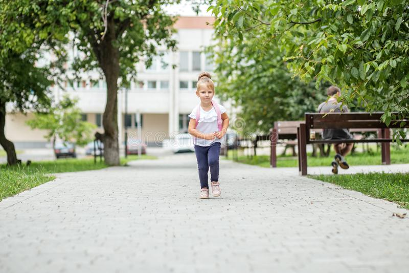 A little girl is walking with a backpack down the street. The concept of school, study, education, friendship, childhood. A little girl is walking with a stock image