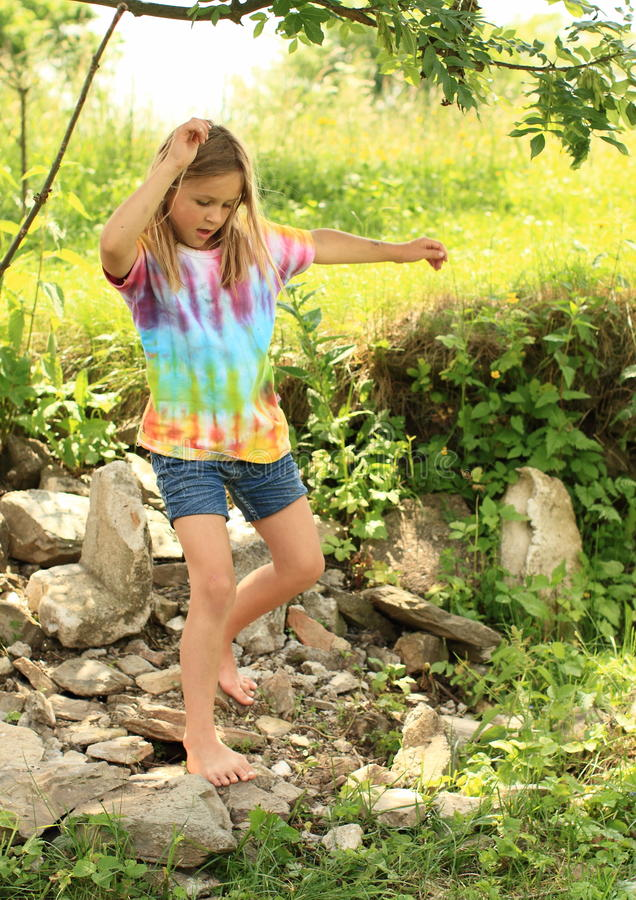 Little girl walking barefoot on rocks royalty free stock image