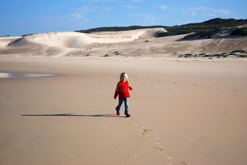 Little girl walking on beach. A cute little caucasian girl child with happy smiling facial expression walking in the sand of a lonely beach in winter times royalty free stock photography