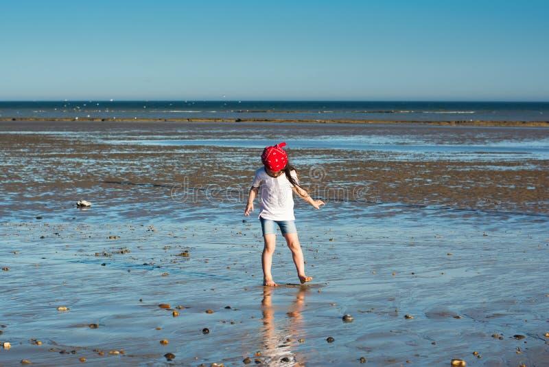 Little girl walking on the beach stock image