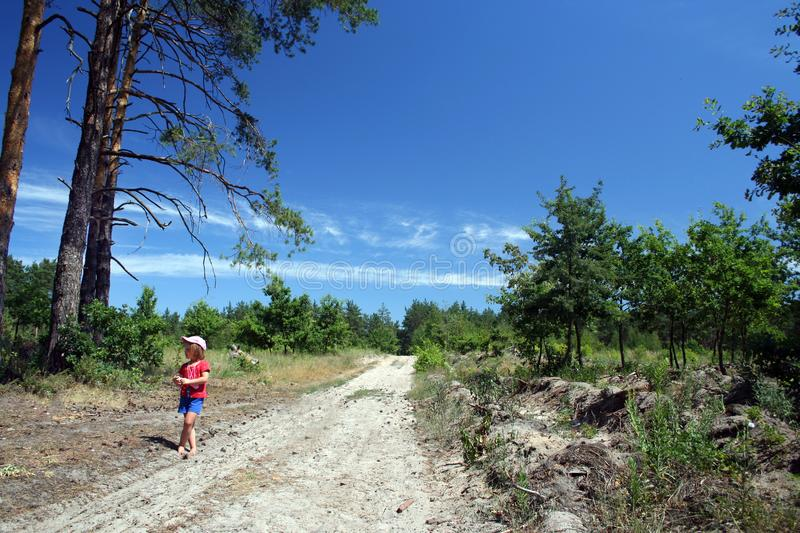 A little girl is walking on the country road barefoot stock image