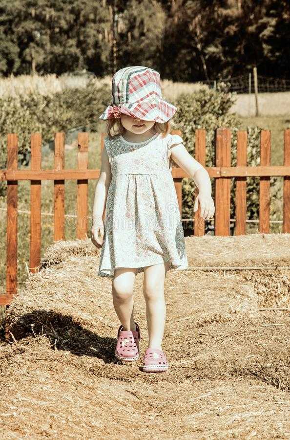 Little girl is walking on the haystack, vintage filter royalty free stock photo
