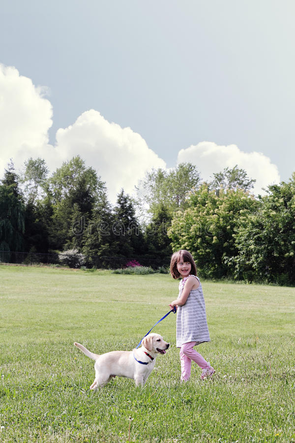 Little Girl Walking her Puppy stock photography