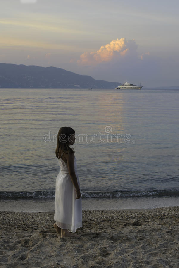 Little girl walking near the sea on sunset royalty free stock image