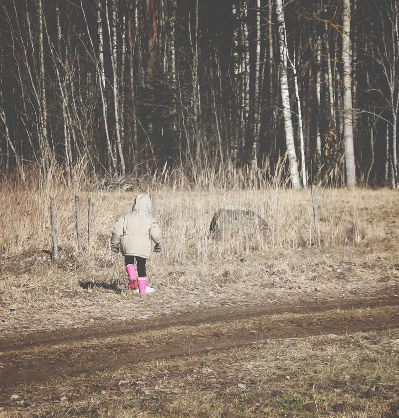 A little girl walking outdoors near the forest stock image
