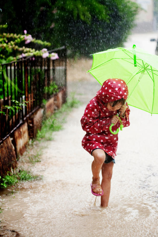 Little girl walking in the rain royalty free stock image