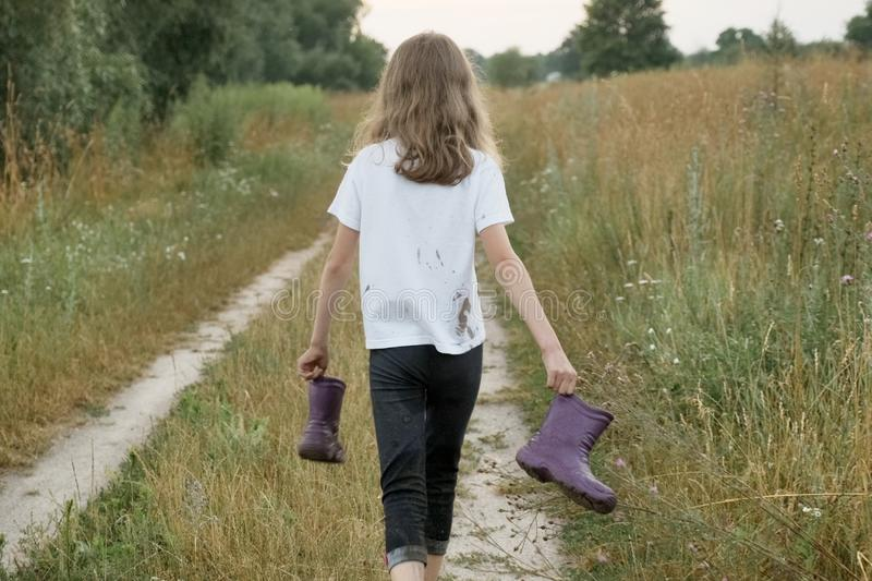 Little girl walking on rural road with rain boots in hands royalty free stock photo
