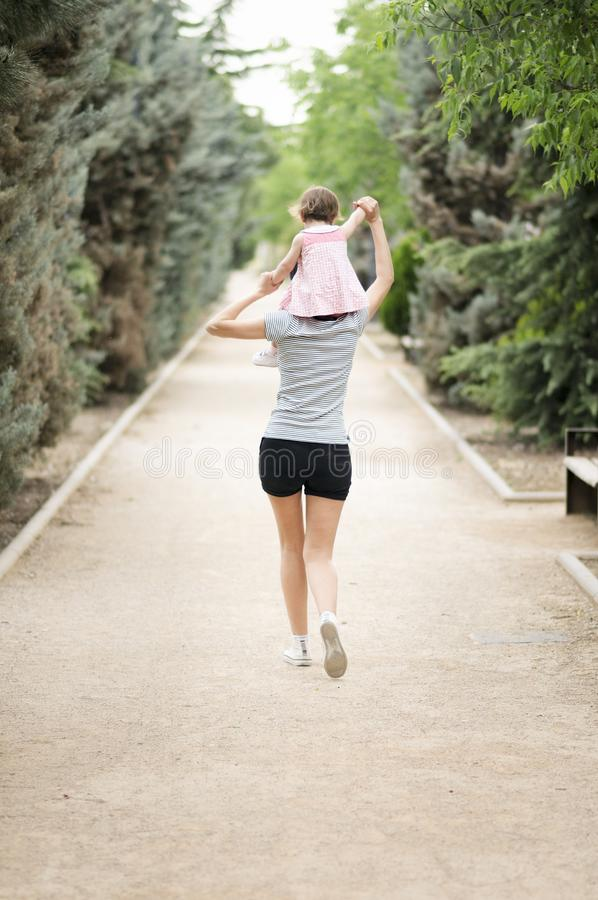 Little girl walking on the shoulders of her mother stock photo