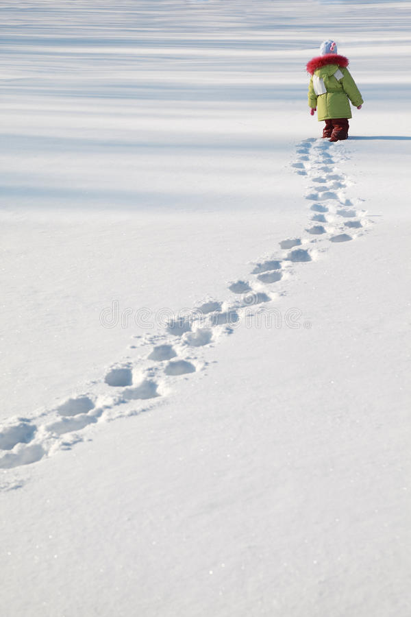 Little girl walking on snow royalty free stock photography