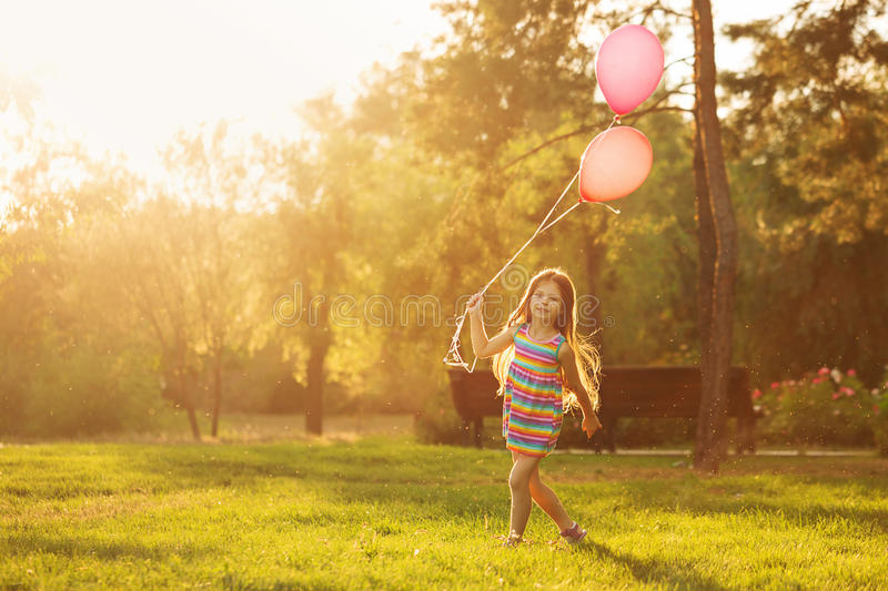 Little girl walks with balloons. Little girl with balloons walking on the lawn in the park outdoors. Freedom and carefree. Happy childhood stock image
