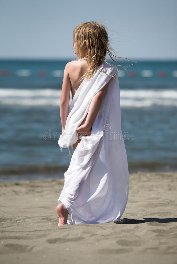 Little girl walks at the beach in white clothes
