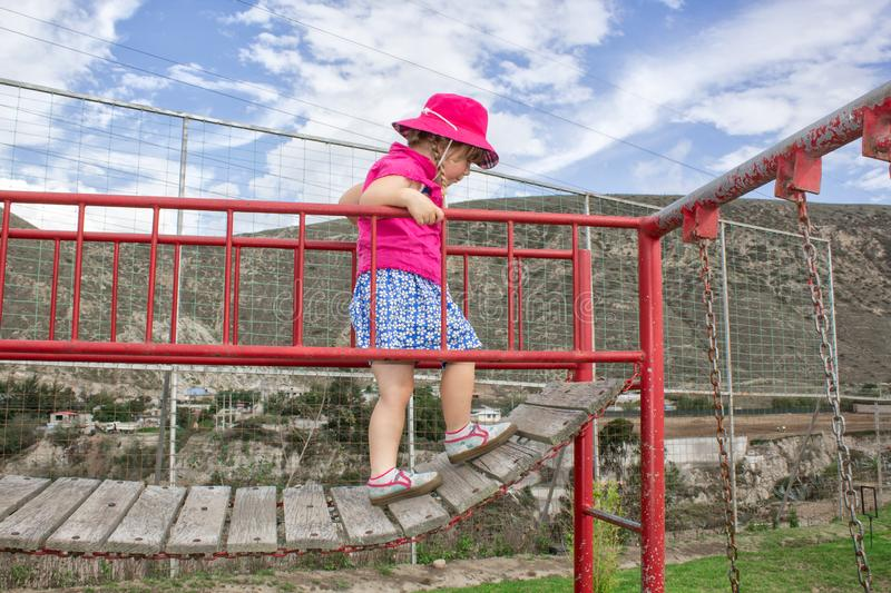 A little girl walks on the bridge in the playground. Children`s entertainment. stock photography