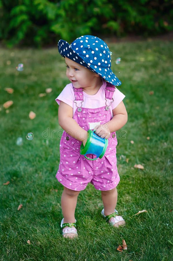 Little girl walks in the park on the grass royalty free stock images