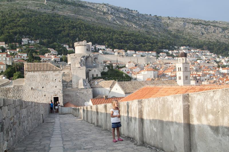 Little girl on the walls enclosing the old town of Dubrovnik at sunset. Croatia, view, red, europe, ancient, famous, blue, mediterranean, sky, architecture royalty free stock images