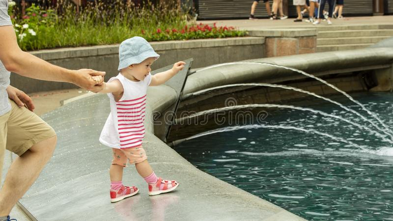 A little girl wants to swim in the fountain. Baby goes to the fountain, pulls his hand to the water. European girl in a hat walk royalty free stock photo
