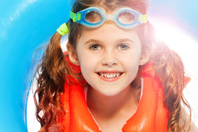 Little girl wants to swim at sunny day. The portrait of cute little girl at swimming eyewear and orange life jacket holding her blue rubber ring royalty free stock images
