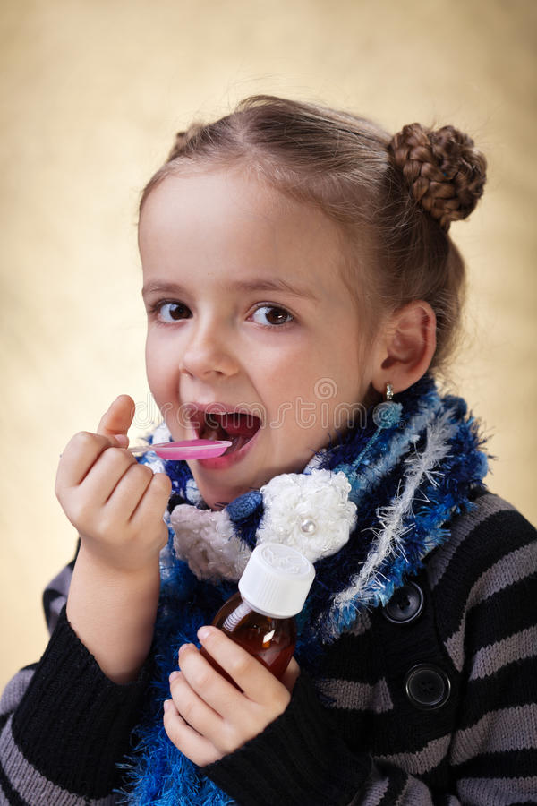 Little girl taking cough medicine syrup stock photography