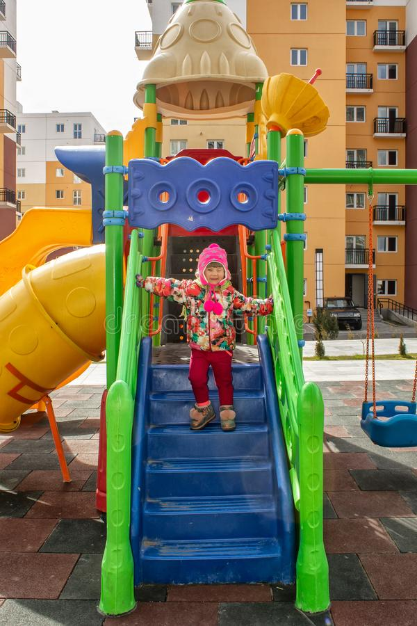 The little girl, warmly dressed, in a hat and jacket plays on the playground with slides and swings in the courtyard of residentia royalty free stock photos