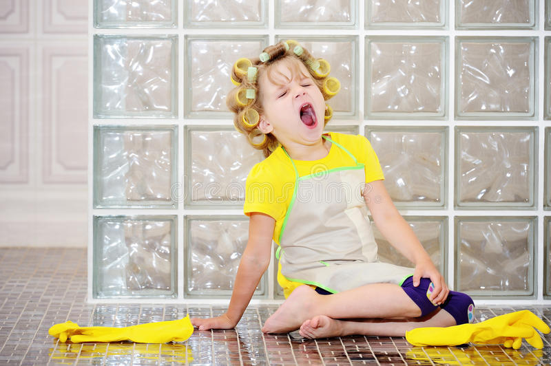 The little girl was cleaning the house. She helped my mother, she was very tired. Yawns. Wants to sleep stock image