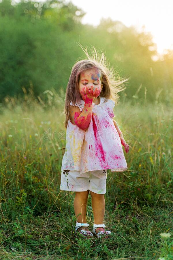 The little girl was covered in paint. a girl in a green clearing. hair up.  stock photography