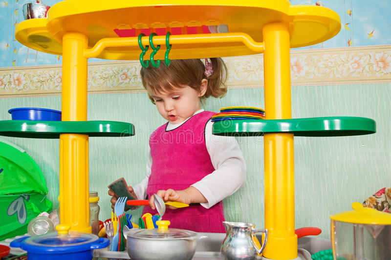 Little girl washes ware. Indoor stock photography