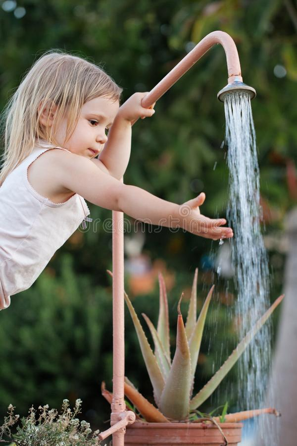 Little girl washing her hands outdoor stock images