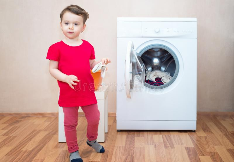 Little girl and washing machine stock photography