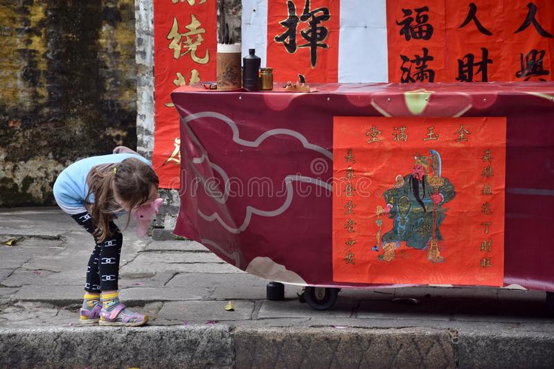 A little girl watches a drawing of chinese general Guan Yu royalty free stock image