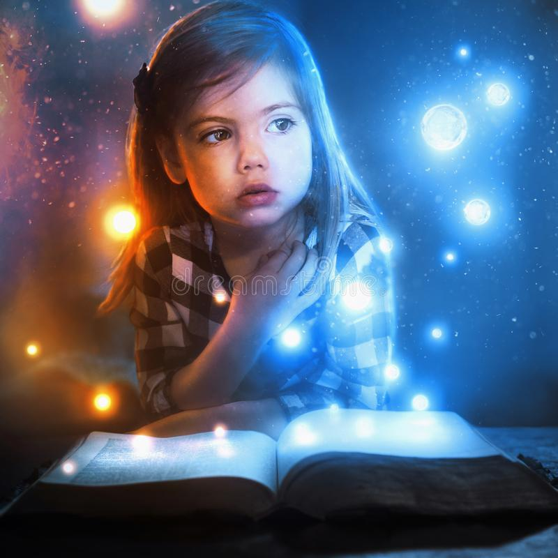 Little girl and glowing lights. A little girl watches glowing lights and stars flow out of an open book stock images