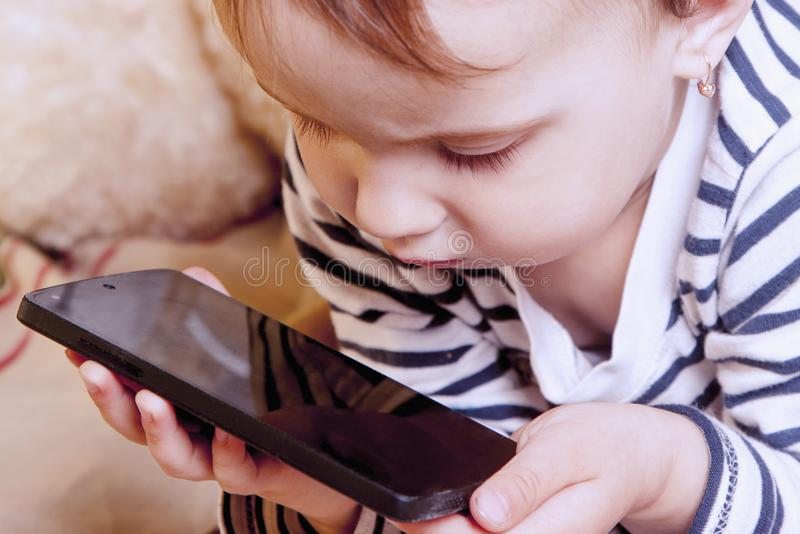 The little girl watching cartoons before bedtime. Happy girl using mobile phone in the bedroom. relaxation, sleep, technology co royalty free stock photos