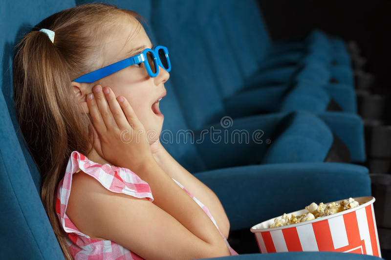 Little girl watching film at the cinema stock photography