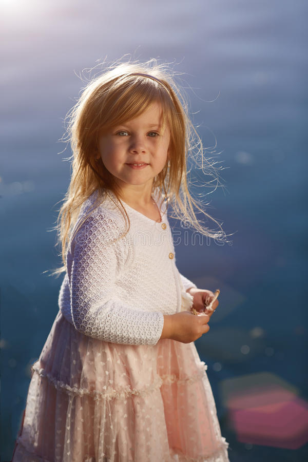 Little girl on the water background, portrait a sunny day royalty free stock photos