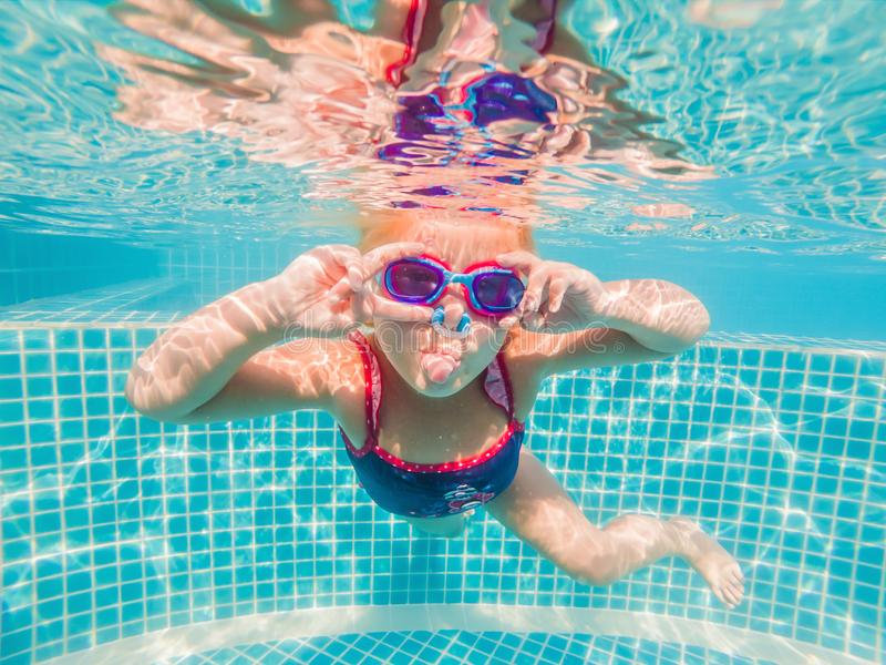 The little girl in the water park swimming underwater and smiling stock images