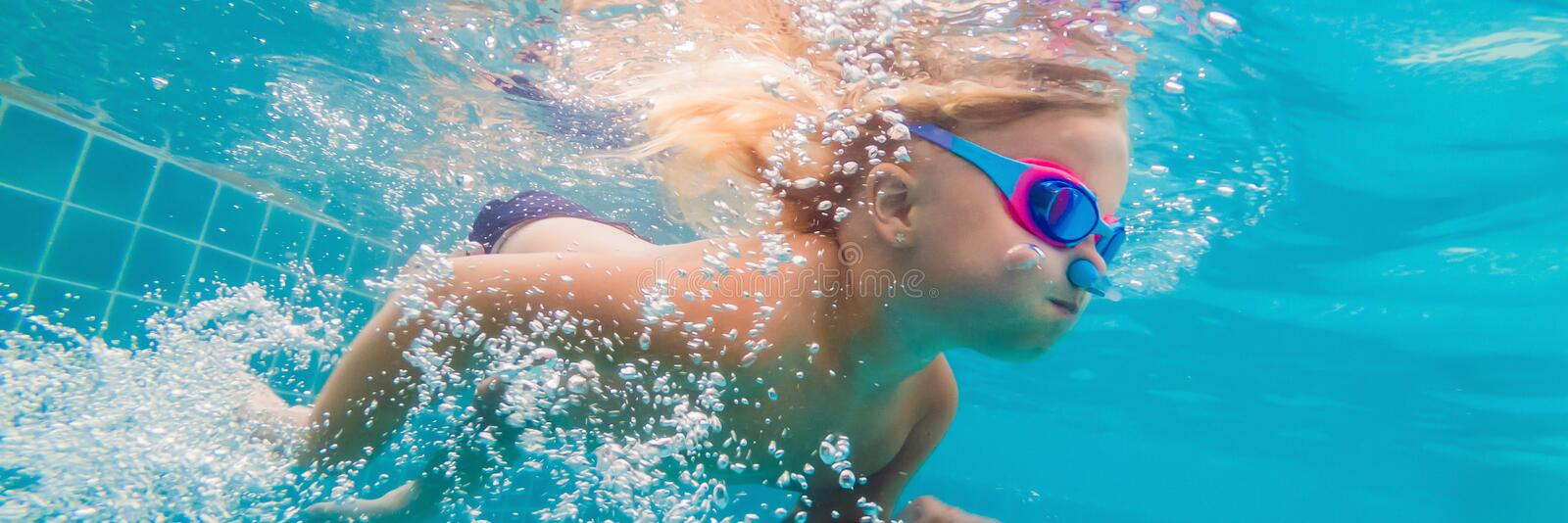 The little girl in the water park swimming underwater and smiling BANNER, LONG FORMAT stock photography
