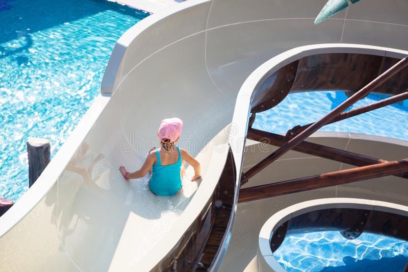 Little girl at the water slide on sun holidays royalty free stock photo