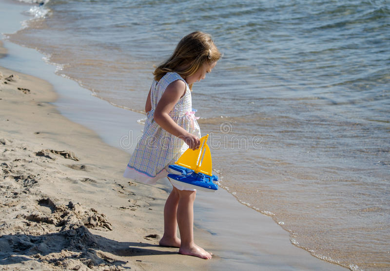 Little girl by the water with toy boat stock image